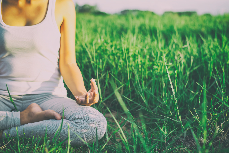 Femme qui fait du yoga en posture du lotus dans l'herbe